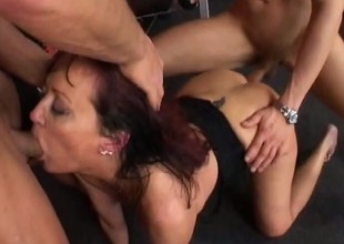 In the gym, a piping hot mature woman gets pounded hard by 2 juvenile chaps