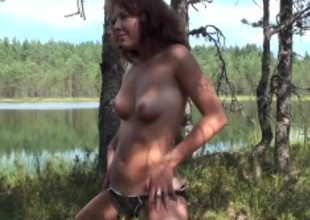 Amateur sweetheart in a swimsuit strips by the lake