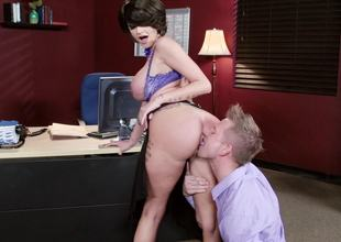 A busty milf with large silicone filled udders is fucked in the office