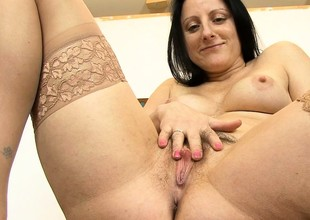 Chubby brunette MILF rubs her hairy cunt with a toy with respect to her office