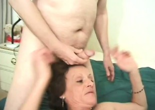Horny granny grabs two thick pricks and works around her mouth
