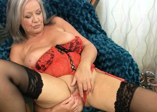 Plumper gray haired granny slips her fingers in her break loose and teases