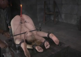 Lit candle in the asshole of a bound girl