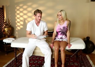 Tattooed busty blonde receives it in doggystyle from masseur