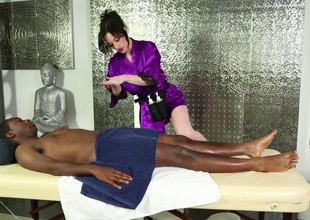 Pale skinned masseuse sucking a black dude's cock on the rub-down table
