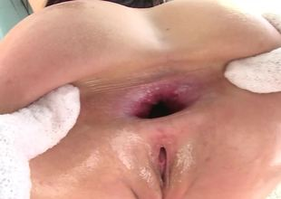A brunette that loves anal is overspread with oil and she is fucked