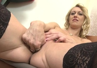 Golden-haired slips two fingers into her mature pussy